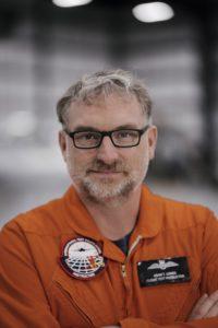 Adam Lowes in orange flight suit.