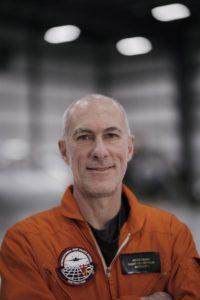 Dr. Andre Celere in orange flight suit.