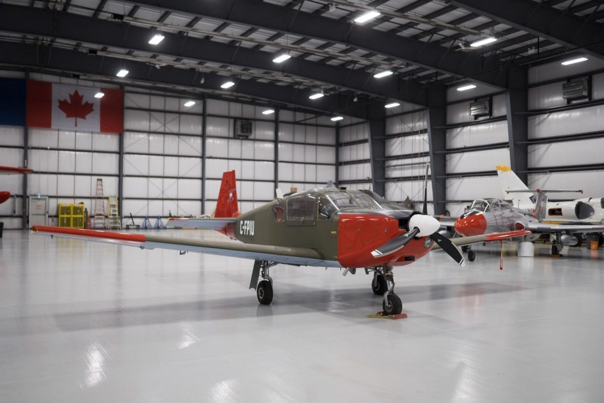 Green and red Brassov airplane in hangar.