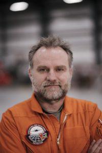Cedric Danancher in orange flight suit in hangar.