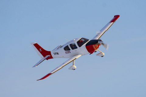 Red and white Cirrus-22 fixed wing plane in sky