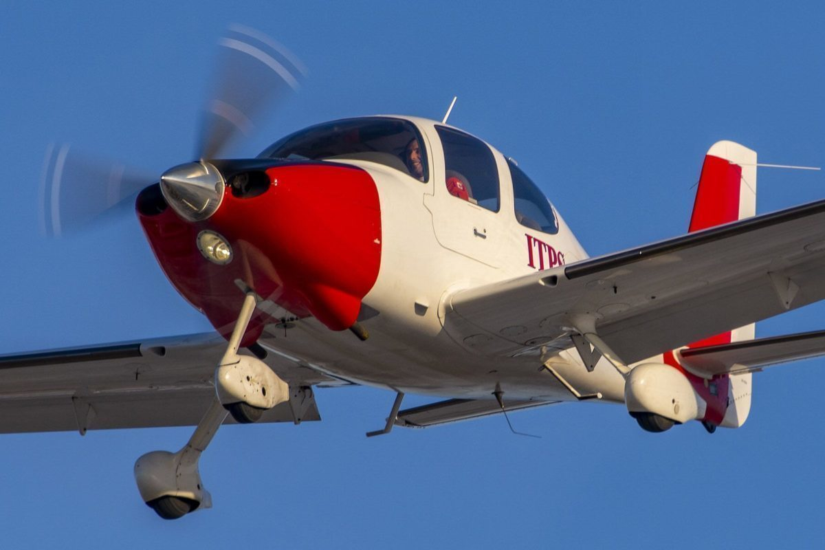 Red and white Cirrus SR22 fixed wing aircraft.