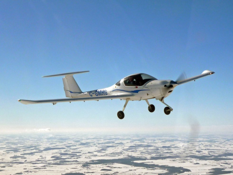 A white DA20-01 aircraft flying in the sky.