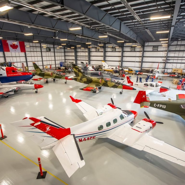 The inside of a hangar full of red tailed and white planes, Canadian flag hung in background on wall.