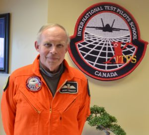 Geoff Connolly in orange flight suit in front of ITPS crest on wall.