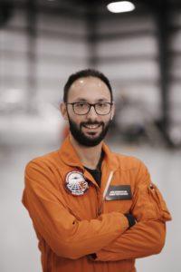 Joao Falcao in orange flight suit in the hangar.