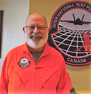 John Turner wearing an orange flight suit in front of ITPS crest on the wall.