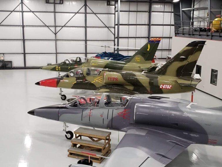 Three Aero Vodochody L39 jet training aircraft in a hangar.