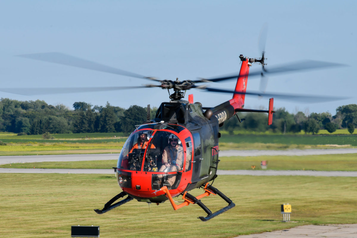 Green and red MBB Bo105 helicopter landing on tarmac.