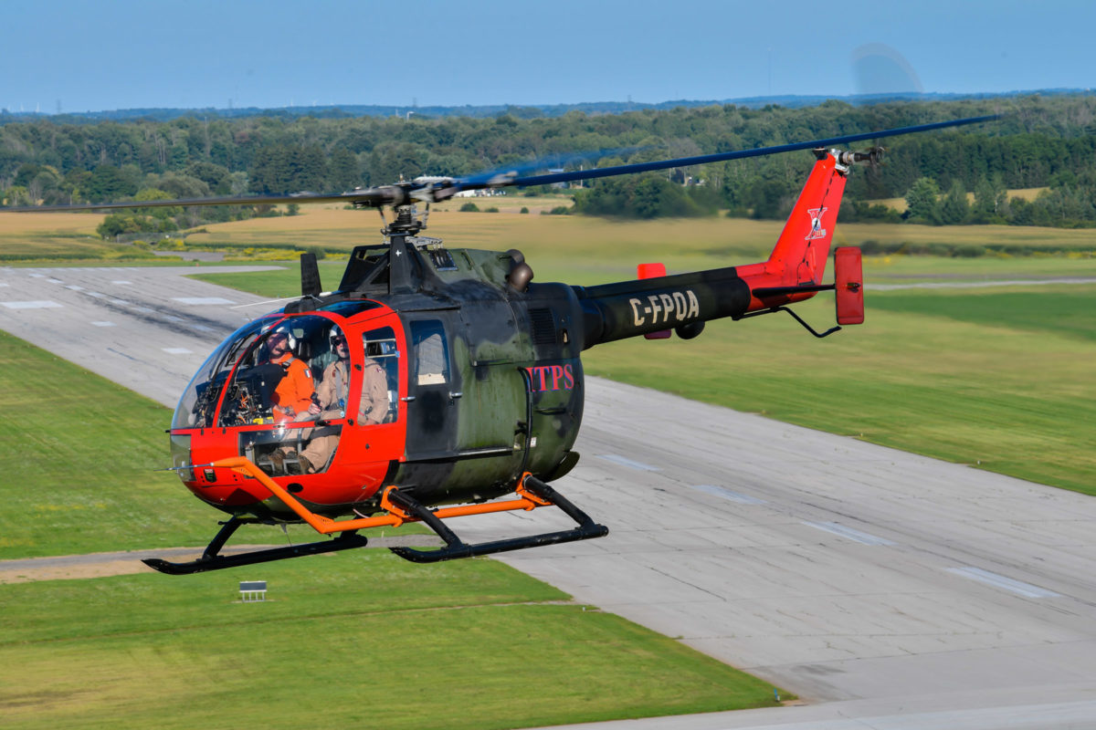 Green and red MBB Bo105 helicopter flying at CYXU