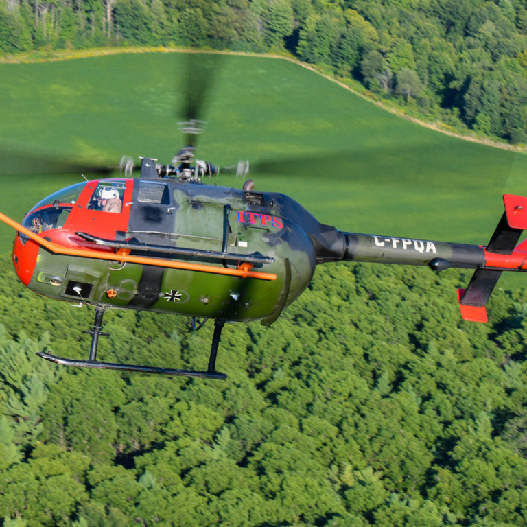 Green and red MBB Bo105 helicopter flying over green landscape
