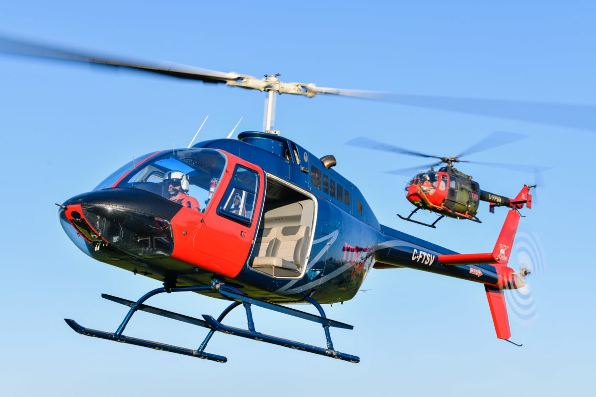 Blue and red Bell B106 helicopter and green and red MBB Bo106 helicopter
