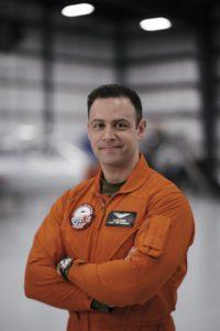 Dr. Panos Vitsas in orange flight suit in hangar.