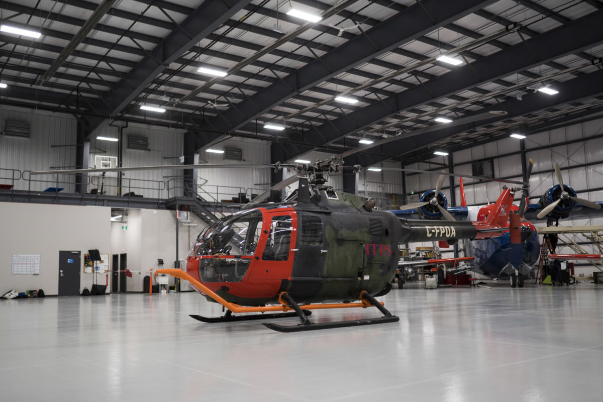 Green and red Bo-105M helicopter in hangar