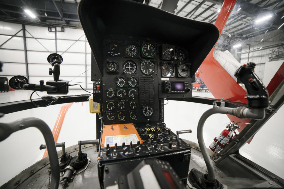 An aircraft cockpit showing many large and small gauges, as well as control knobs, on a black interface.