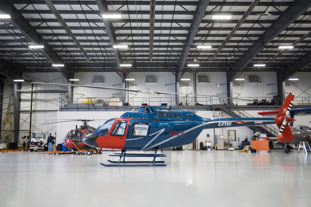 Blue and red Bell B106 helicopter in the hangar