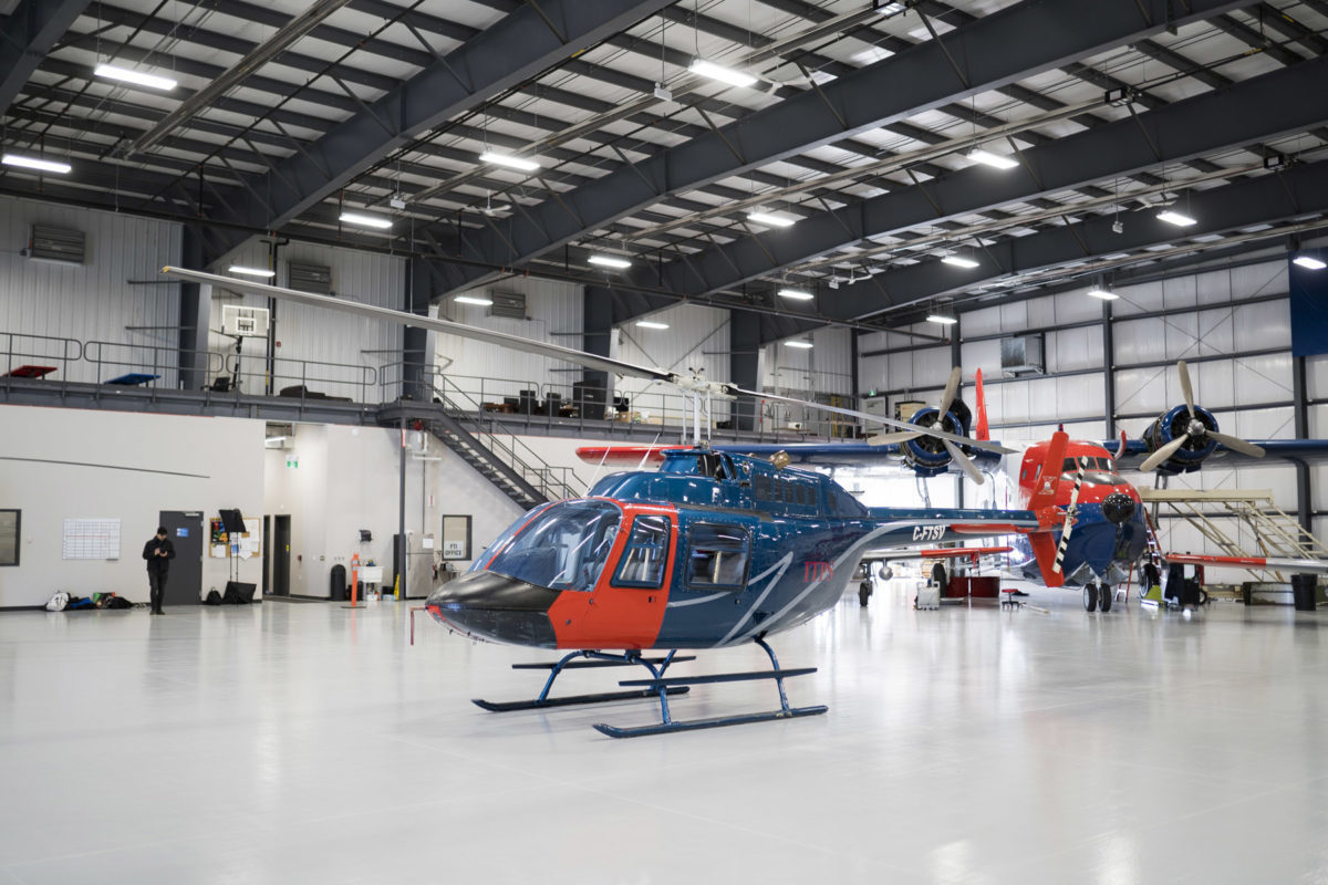 Blue and red Bell B106 helicopter in hangar