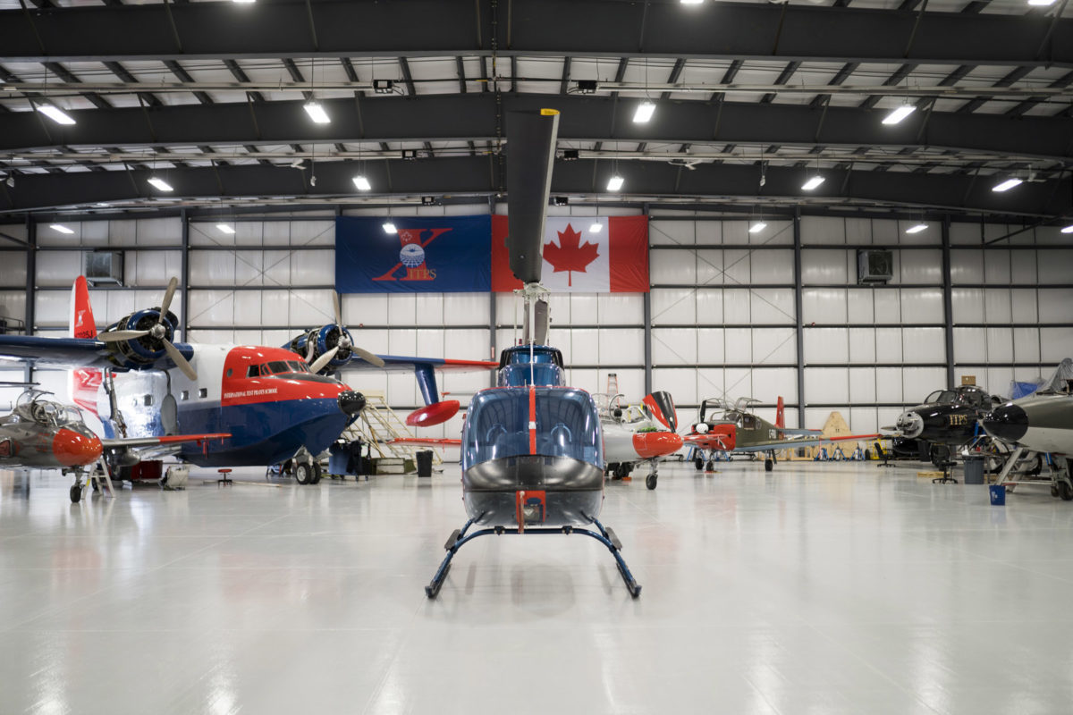 Blue and red Bell B106 helicopter with other aircraft in the ITPS hangar.