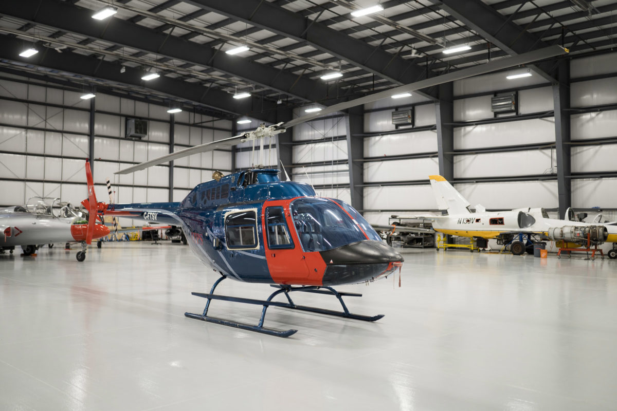 Blue and red Bell B106 helicopter in hangar.
