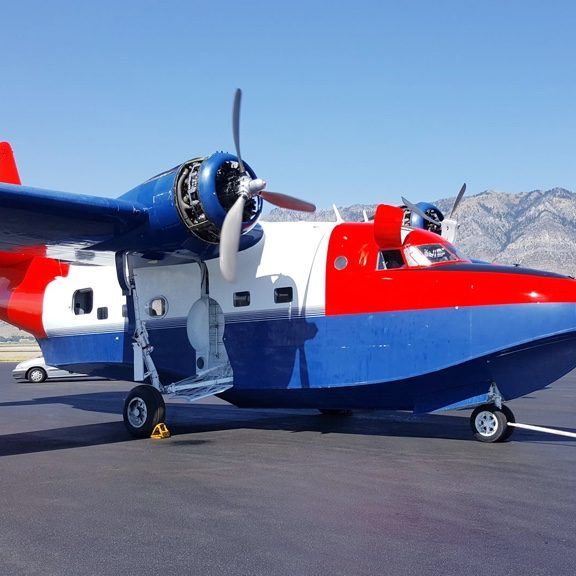 White, red and blue ITPS HU-16 Sea Plane parked on tarmac in front of mountains