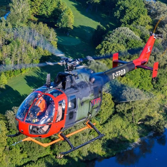 ITPS Canada - Fleet Bo105 007 green and black helicopter with red nose and tail Flying Over Golf Course