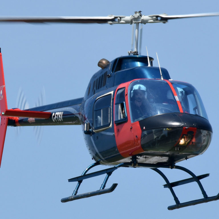 Blue and red Bell B106 helicopter hovering over the ground.