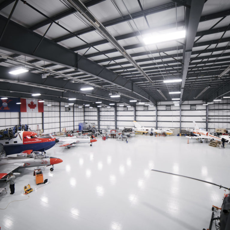 Airplane hangar with multiple planes and helicopters.