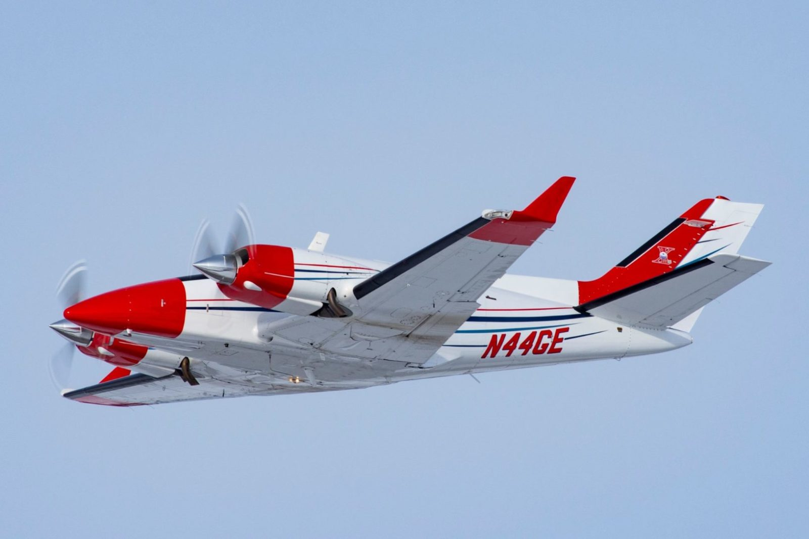 Red and white Duke B60 airplane flying in the air.