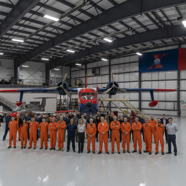 Group of ITPS personnel stand in front of a cherry red and navy blue float plane.