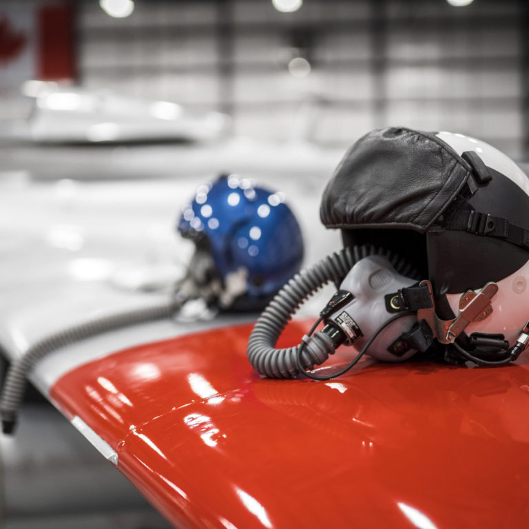 ITPS personnel helmets rest on a red and white striped wing of an aircraft in the hangar.