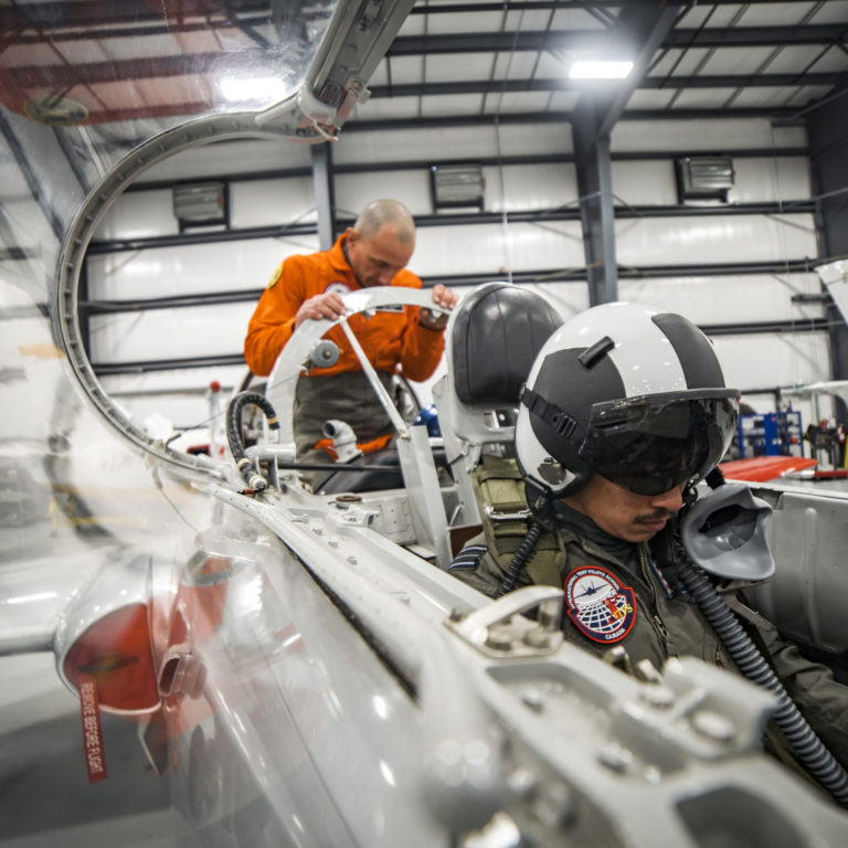ITPS students and teachers practice onboarding on a silver, parked plane in the hangar.