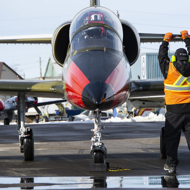 Ground crew on the air apron handle a black nosed, red paneled ITTC L-39.