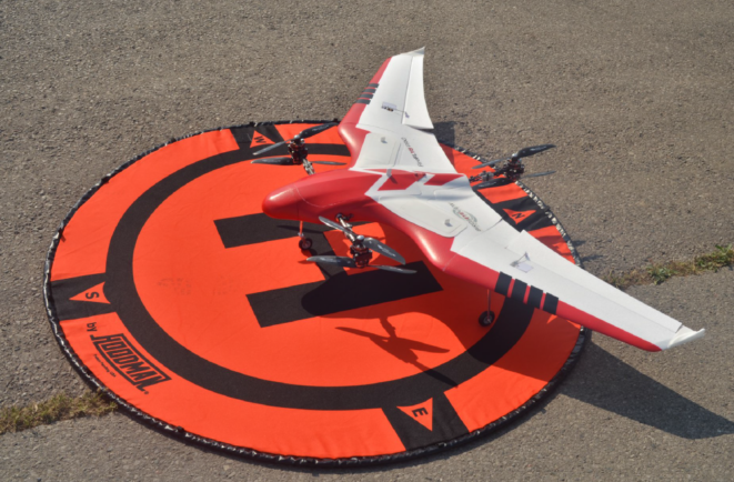 Red and white unmanned aerial system sitting in a target.