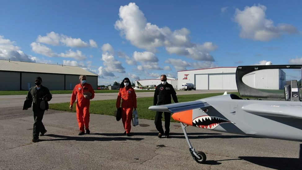 Students and flight test instructors with grey and orange manned remote piloted aircraft