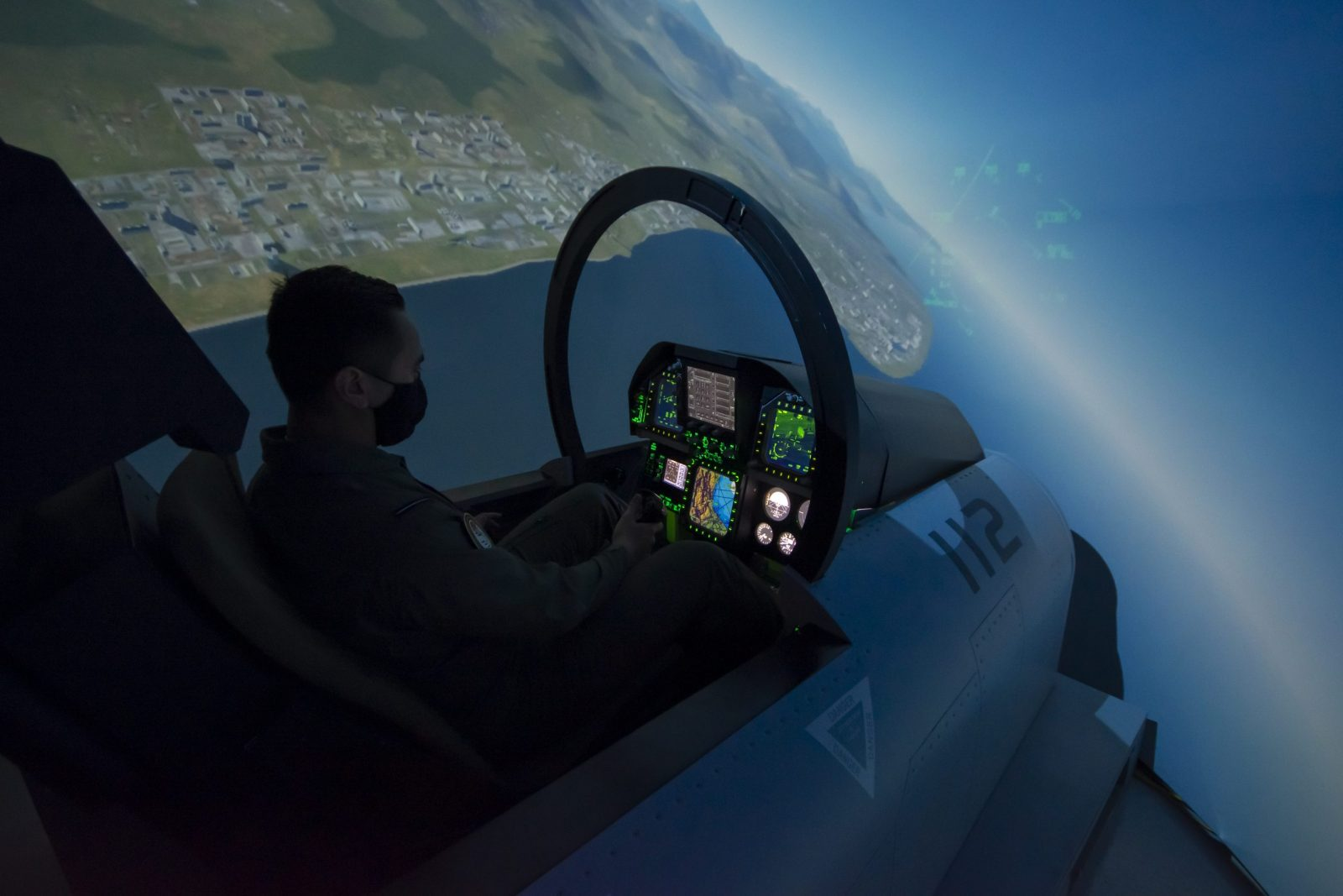 Student in green flight suit using F-18 aircraft simulator