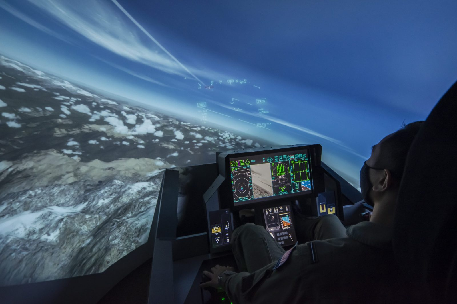 ITPS student in green flight suit using F-18 aircraft simulator