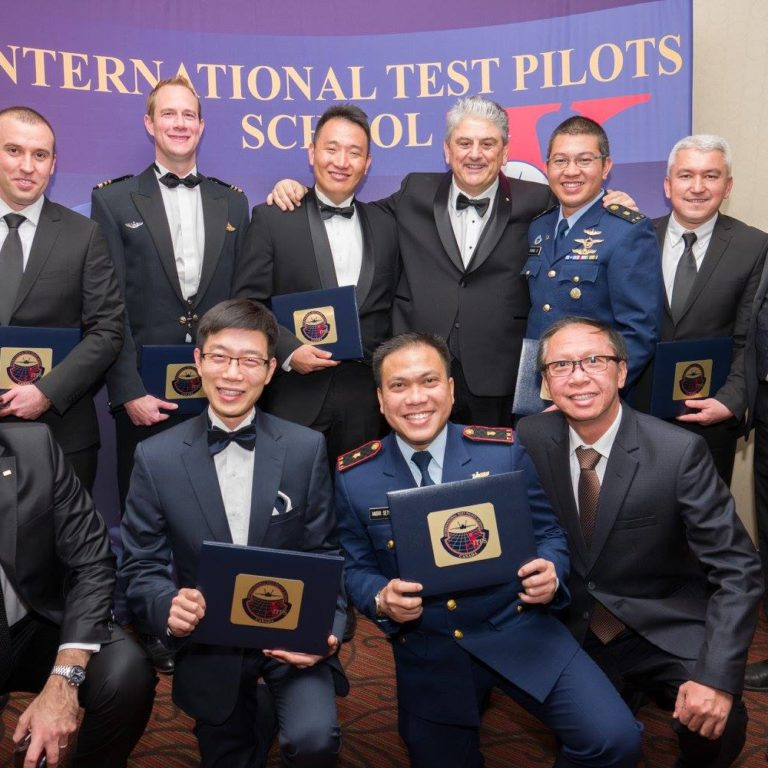Test pilot graduates at ITPS Annual Flight Test Seminar. Men in military dress and business suits.