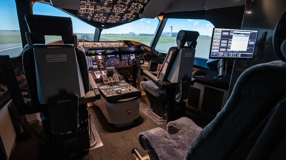 Cockpit of a B787 simulator fully lit up.