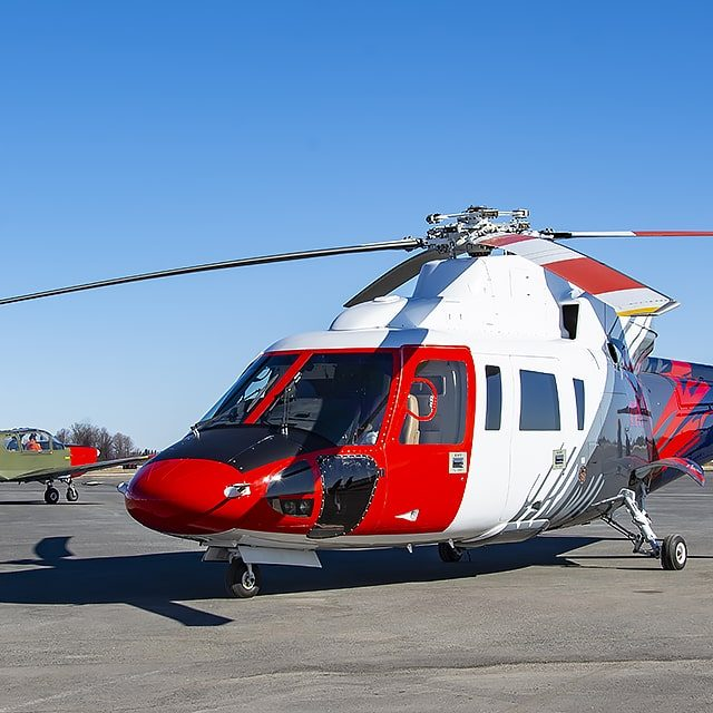 S76 Sikorsky red, white and grey helicopter sitting on the tarmac at International Test Pilots School