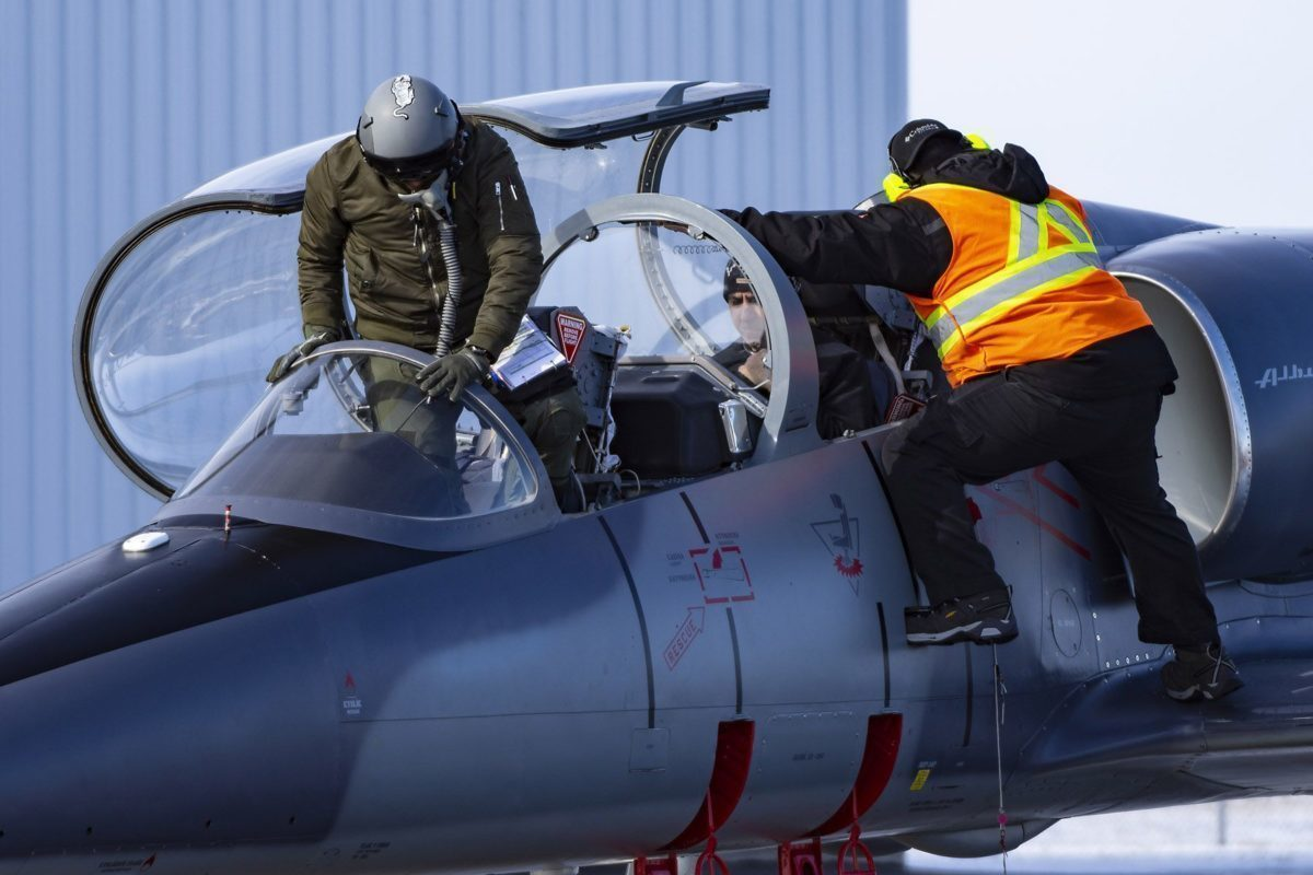 A male ITTC student boarding a grey L-39.