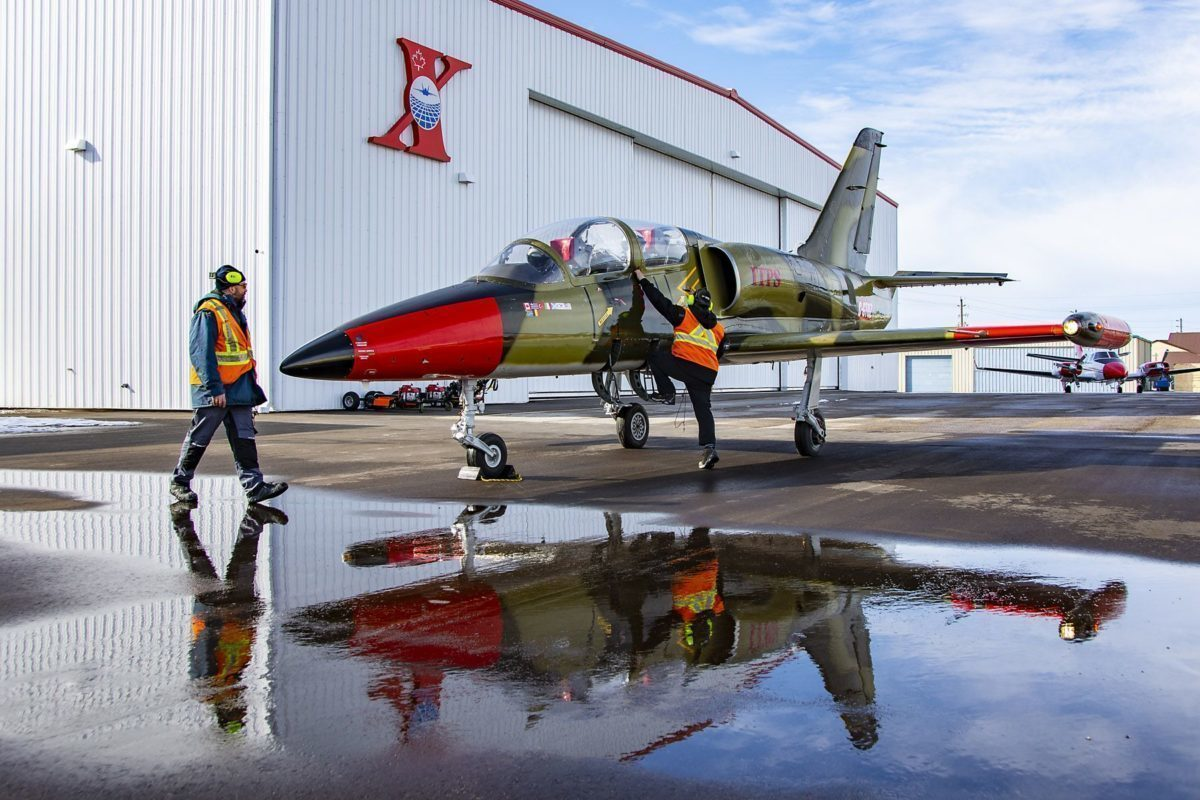 A red and green-coloured Aero Vodochody L-39C military aircraft parked with two grounds crew personnel inspecting the aircraft.