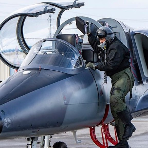An ITTC student boarding a grey L-39 on our air strip.