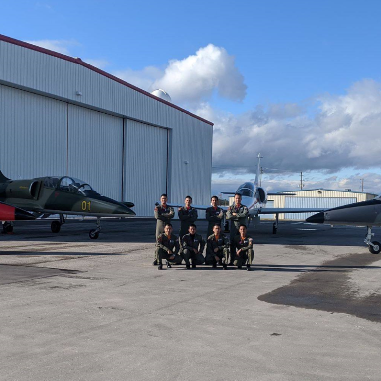 Eight ITPS students at our facility on tarmac; planes and hangars surround them.