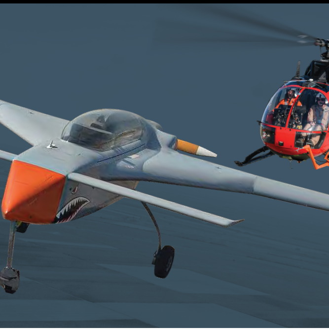 A grey and orange UAV in flight with a red and black helicopter behind it.